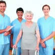 Stock Video: Elderly womsmiling with her physical rehab team