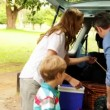 Family unloading their car for a camping trip on a sunny day — Vidéo