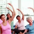 Stock Video: Smiling women doing yoga in fitness studio
