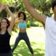 Stock Video: Fitness class doing star jumps in the class