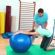Trainer helping his client stretch her back with exercise ball — Stock Video