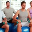 Fitness group sitting on exercise balls lifting hand weights — Stock video