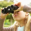 Stock Video: Cute little girl using binoculars in park