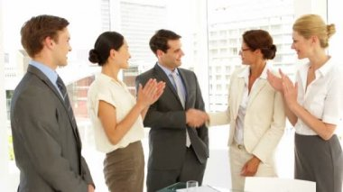 Business people shaking hands at interview while others clap — Stock Video