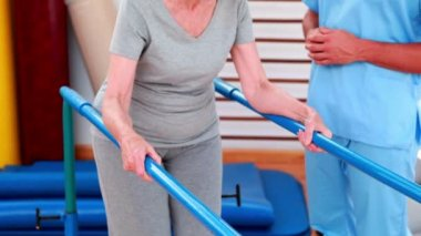 Physical therapist watching patient walk with parallel bars — Stock Video