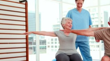 Senior citizens working out with physiotherapist — Stock Video