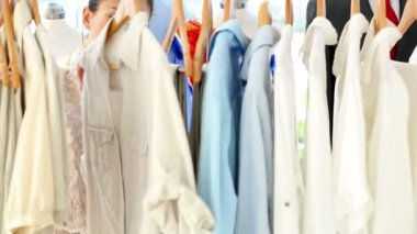 Fashion designer looking through her clothing rail — Stok video