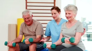 Happy senior citizens exercising with physiotherapist — Stock Video