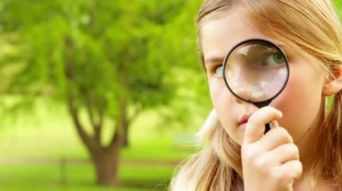 Cute little girl using magnifying glass in park — Stock Video
