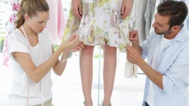 Fashion designers adjusting hemline of dress on a model — Stock Video