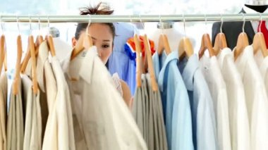 Fashion designer looking through her clothing rail — Stock Video