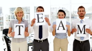 Business people holding pages spelling out team — Stock Video