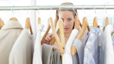 Fashion designer looking at clothes on rail — Stok video