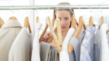 Fashion designer looking at clothes on rail — Stock Video
