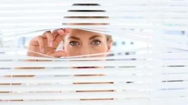 Stern businesswoman peeking through the blinds — Stock Video