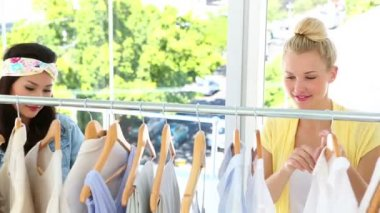 Pretty friends looking through clothing rail together — Stok video