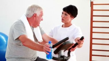 Elderly man using the exercise bike talking to physiotherapist — Stock Video