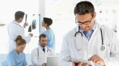 Médico usando tablet enquanto funcionários estão trabalhando por trás dele — Vídeo stock