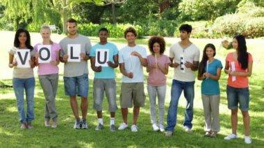 Friends holding letters spelling volunteer — Stock Video