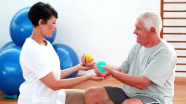 Smiling physiotherapist squeezing massage balls with patient — Stock Video