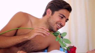 Man tickling his blonde girlfriend with a rose on bed — Stock Video