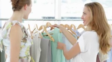 Two pretty friends looking through clothes rails — Stock Video