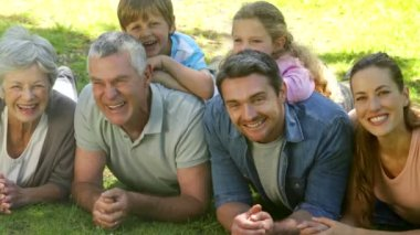 Multi generation family smiling and lying on ground in a park — Stock Video