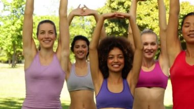 Fitness class stretching their arms and squatting together — Stock Video