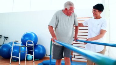 Smiling physiotherapist helping patient walk with parallel bars — Stock Video