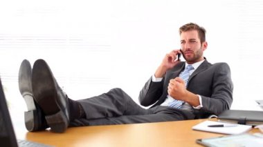 Relaxed businessman putting his feet up talking on the phone — Stock Video