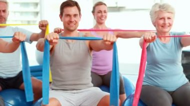 Group sitting on exercise balls stretching resistance bands — Vídeo de stock