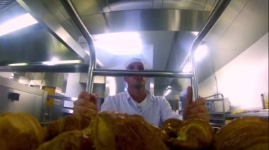 Young baker pushing a trolley or croissants — Stock Video