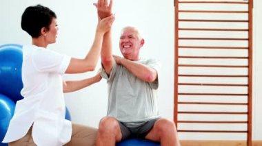 Ler sjukgymnast hjälpa äldre patienter stretch arm — Stockvideo