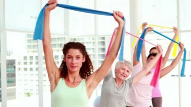 Women stretching resitance bands at a fitness class — Stockvideo