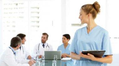 Infirmière, souriant à la caméra, tandis que le personnel parlent derrière elle — Vidéo