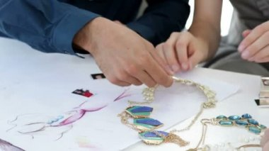 Design team looking at costume jewelry — Stock Video
