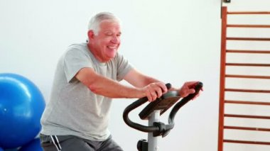 Elderly man using the exercise bike — Stock Video