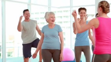 Aerobics class stepping and laughing together — Stock Video