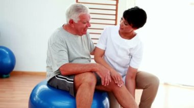 Smiling physiotherapist helping elderly patient bend knee — Stock Video