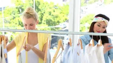 Friends looking through clothing rail together — Stok video