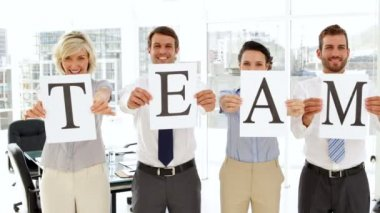 Business people holding up pages spelling out team — Stock Video