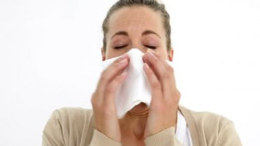 Beautiful sick woman sneezing using a tissue — Stock Video