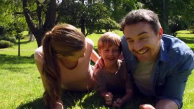 Little boy and parents smiling at camera in the park — Stockvideo