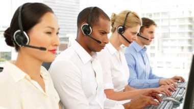 Call centre agents working with one smiling at camera — Stock Video