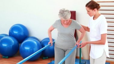 Physical therapist helping patient walk with parallel bars — Stock Video