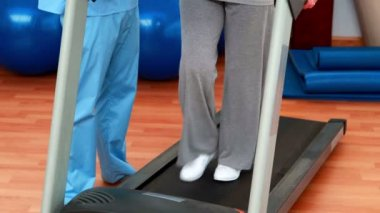 Physical therapist showing patient how to use treadmill — Stock Video