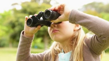 Cute little girl using binoculars in park — Stock Video