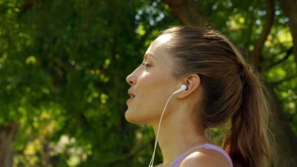 Corredor de agua potable y escuchar música en el parque — Vídeo de stock