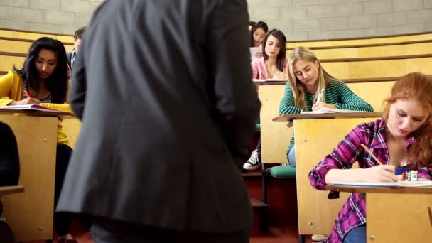Lecturer supervising an exam in lecture hall — Vidéo