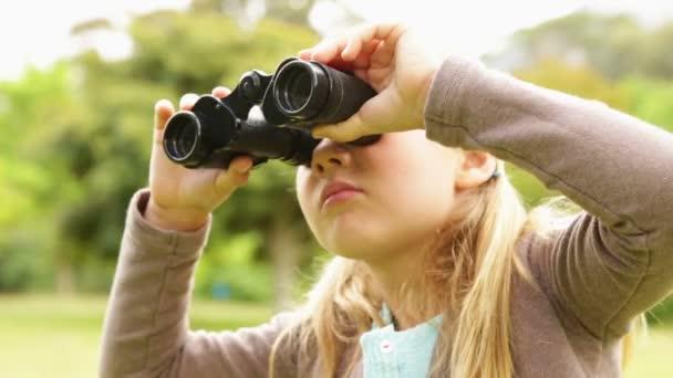 Niña linda utilizando binoculares en el parque — Vídeo de stock
